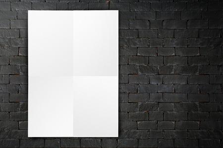 El cartel en blanco papel doblado que cuelga en la pared de ladrillo negro, Plantilla maqueta para añadir su diseño. Foto de archivo - 38084275