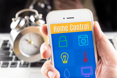 home lighting: Hand holding smart phone with home control application with clock and computer at background, Smart home concept.