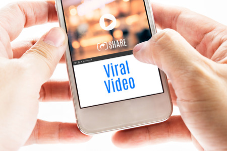 social commerce: Close up Two hand holding smart phone with Viral Video word and icons, Digital concept. Stock Photo