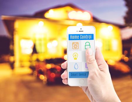 smart: Hand die slimme telefoon met home control applicatie met onscherpte home achtergrond, Slimme woning concept.