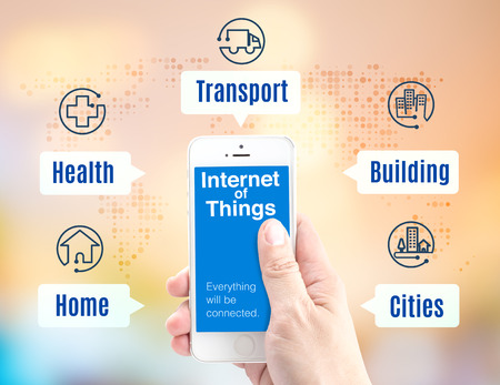 Hand holding smartphone with Internet of things (IoT) word and application icon on blur background, Digital Marketing concept.