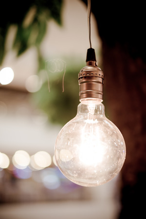 tungsten: .vintage tungsten lightbulbs hanging on tree with bokeh background Stock Photo