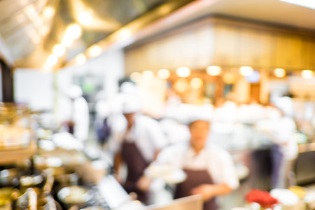 Blurred background : Groups of Chef cooking in the open kitchen,customer can see they cooking at food counter, cooking chef with light bokeh. photo