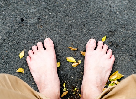 stone steps: bare foot on black stone and dried leaves.
