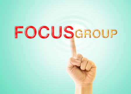 focus group: Index finger touch to the word  FOCUS GROUP  on light green background.