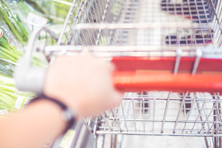Hand holding shopping cart at fresh supermarket blur background with bokeh light. photo