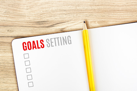 setting goal: Goals Setting word on notebook lay on wood table,Template mock up for adding your goal.
