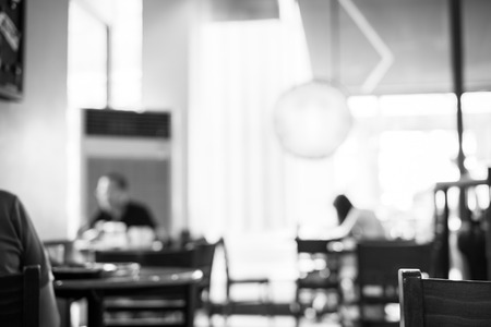 Blurred background  People in Coffee shop blur background with bokeh light with black and white filter. Imagens