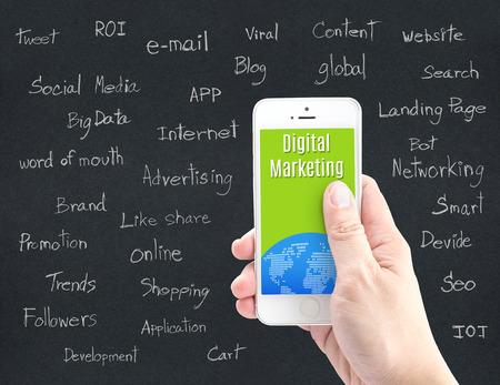 mercadeo en red: Mano que sostiene el tel�fono inteligente con Marketing Digital palabra y palabra sobre marketing digital en papel negro, el concepto de Marketing Digital. Foto de archivo
