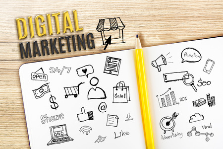 seo marketing: Open Notebook on wooden desk with icon relate with Digital Marketing, Business concept. Stock Photo