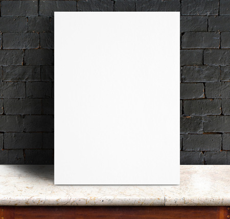 Black White paper poster lean at black brick wall and marble table,Template mock up for adding your text. photo