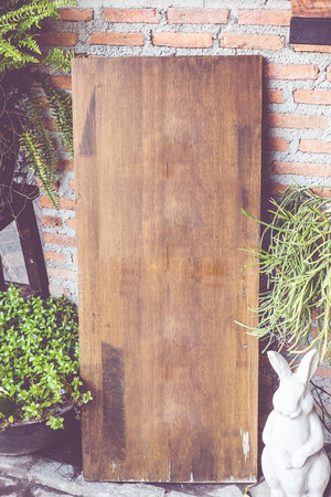 signboard: vintage filter : Empty wood sign board on brick wall in front of coffee shop,Template mock up for adding your menu of restaurant.
