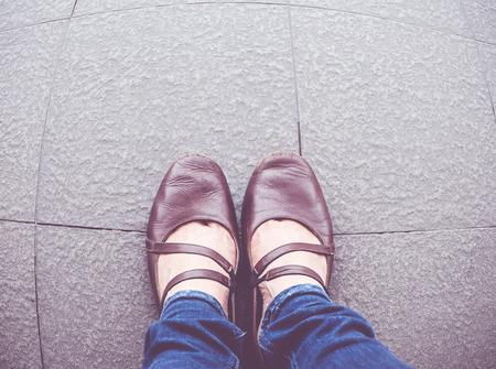 suolo: Filtro veduta aerea Vintage di scarpa donna indossare blu jean stare sul marciapiede.