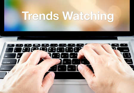 business trending: hand type on laptop with trends watching on screen with blur background, online business concept.