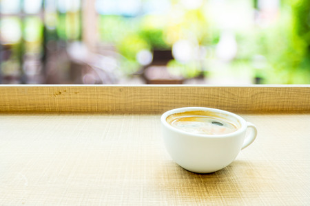 bar top: Espresso Coffee cup on wood table in cafe with blur garden background, Leisure lifestyle concept