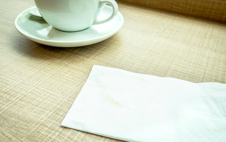 bar top: Vintage filter : Tissue paper with coffee stain and coffee cup on wood table Stock Photo
