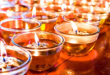 votive candle: Pray candle glass on wood table in chinese temple. Stock Photo