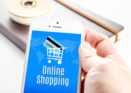 Close up hand holding smartphone with Online shopping word and credit card in cart icons, Business Marketing concept. photo