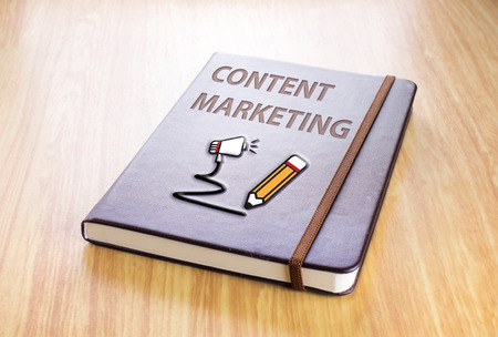 content management: Brown notebook with Content marketing word and pencil with speaker icon on wood table, Technology concept.