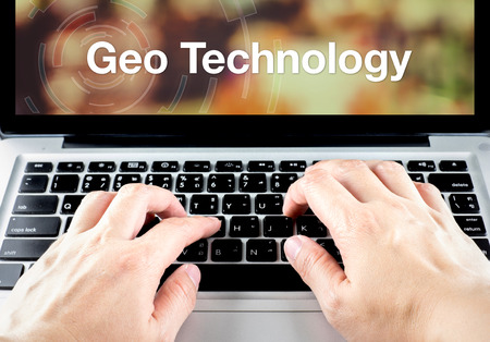 Geo-technologie woord op notebook scherm met type hand op het toetsenbord, Location-technologie concept.