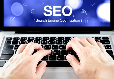 search engine optimization (SEO) word on notebook screen with hand type on keyboard, SEO business concept. photo