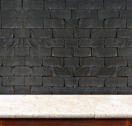 Empty marble table and white black brick wall in background. product display template.