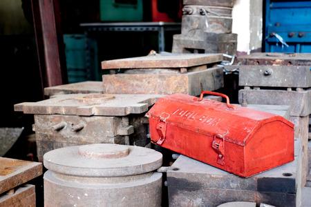 lunares rojos: grunge caja de herramientas de metal rojo en lunares rústicos en fábrica. Foto de archivo