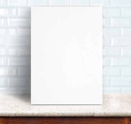 Black White paper poster lean at white ceramic tiles wall and marble table,Template mock up for adding your design. photo