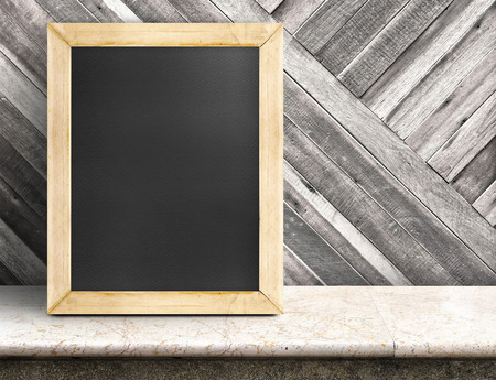 beside table: Blank blackboard on marble table at diagonal wooden wall,Template mock up for adding your design and leave space beside frame for adding more text. Stock Photo