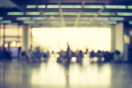 Blur background : Passenger waiting for flight at airport terminal blur background with bokeh light.
