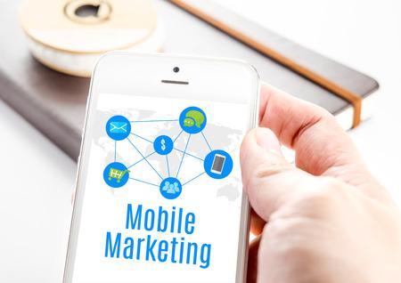 redes de mercadeo: Cierre de la mano que sostiene el teléfono inteligente con la palabra Marketing móvil y los iconos con el cuaderno en el fondo, la tecnología concepto de negocio móvil