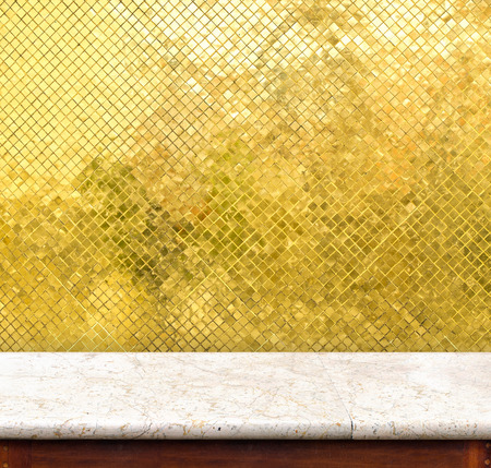 decoraton: Empty marble table and golden tiles wall in background,product display business template