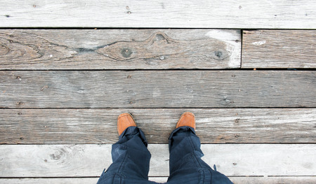top down: aerial view of human stand on wooden plank floor. Stock Photo