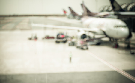 air traffic: Blurred background : looking through terminal window to see airplane at airport.