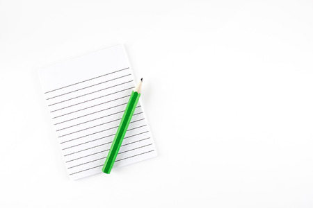 foglio a righe: Vista dall'alto del Governato blocco note di carta con la matita verde su sfondo bianco Lascia spazio per aggiungere il contenuto ..