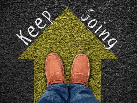 """영감 인용 : 이동 앞으로 파란색 화살표, 동기 부여 인쇄상의와 도로에 신발의 공중보기에 """"계속하세요""""."""