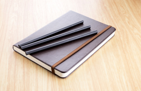 hard cover: Three Black pencil on Brown Hard cover notebook with elastic strap on wooden table in perspective view.