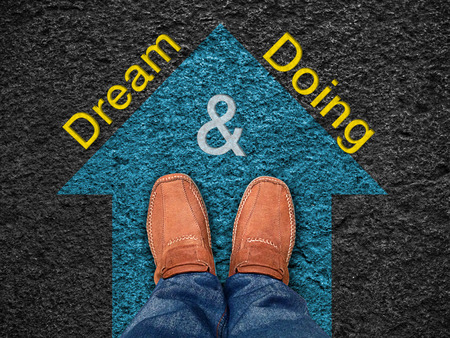 motivation: Inspiration quote :  Dream & Doing on aerial view of shoe on road with move forward blue arrow ,Motivational typographic.