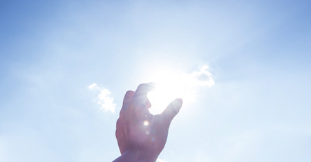 Hand picking sun at blue sky and cloud. Stock Photo