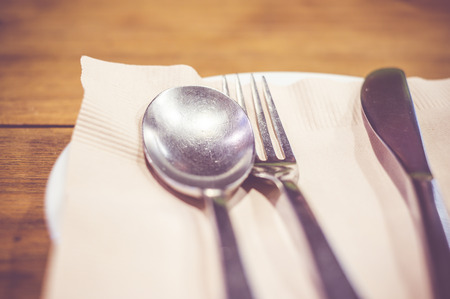 settings: Vintage filter : Close up spoon,fork,knife on dinner table. Stock Photo