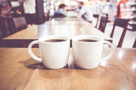 tazas de cafe: Filtro vintage, par de Blanco taza de caf� en la mesa de madera con caf� borrosa luz de fondo bokeh. Foto de archivo