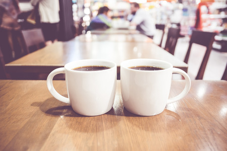 two person: Vintage filter, couple of White coffee cup on wood table with blurred cafe bokeh light background.