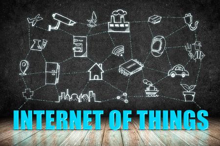 Internet of Things (IoT) word op houten vloer met doodle pictogram op het bord muur, Technology Concept Design. Stockfoto
