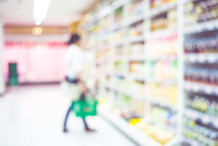 food distribution: Blur background of woman customer select product on shelf in supermarket.