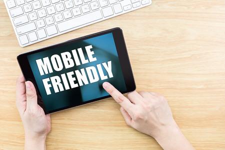 Finger clic en la pantalla con la palabra amable móvil con teclado en mesa de madera, diseño web Responsive.