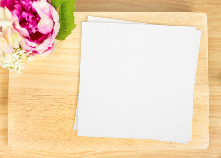 trompo de madera: Top view of Blank wooden plate with white paper and flower pot on table top