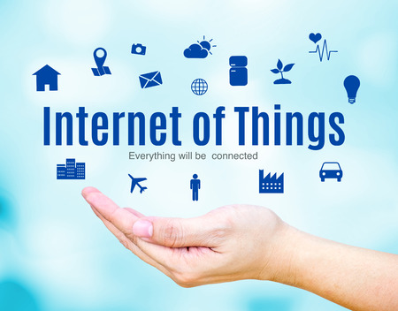 Open hand with Internet of Things (IoT) word and icon on blue blur background, Technology concept.