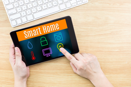 internet: Finger click screen with Smart home application interface with keyboard on wooden table,Internet Business concept Stock Photo