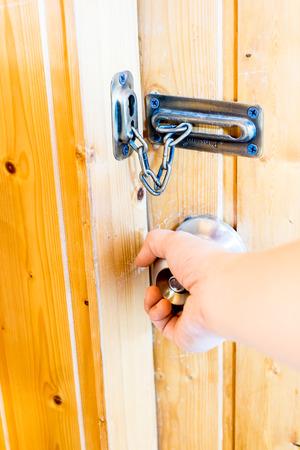 room door: Hand opening door knob door at wooden room. Stock Photo