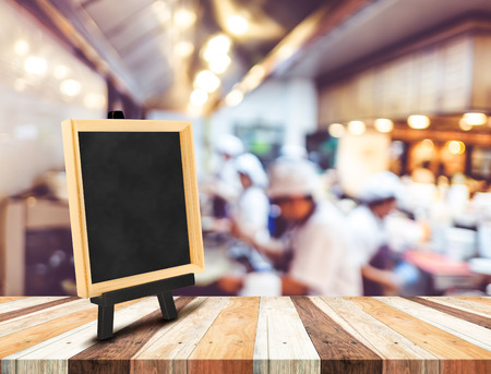 Blackboard menu with easel on wooden table with blur open kitchen at  restaurant background, Copy space for adding your content. Stock Photo
